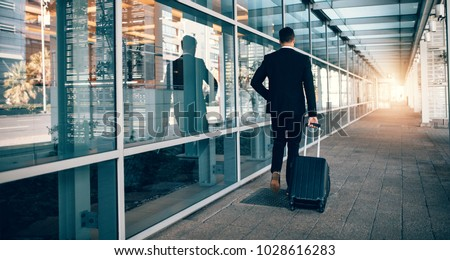 Rear view of young businessman walking outside public transport building with luggage. Business traveler pulling suitcase in modern airport terminal.