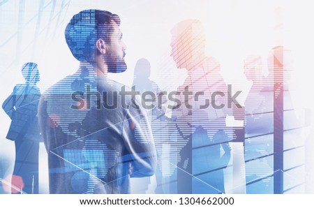 Rear view of young businessman with beard looking at skyscrapers with his colleagues silhouettes and double exposure of world map. Toned image. Elements of this image furnished by NASA #1304662000