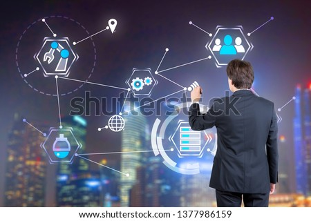 Rear view of young businessman working with GUI interface over blurred night cityscape background. Concept of hi tech in business. Double exposure #1377986159