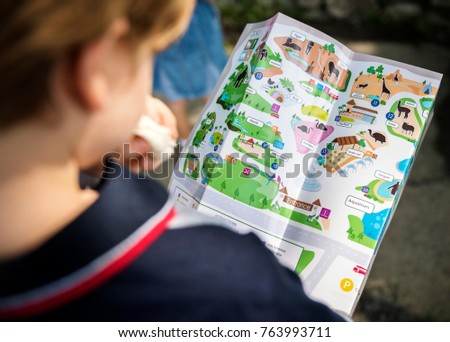 Rear view of young caucasian boy looking at the zoo map