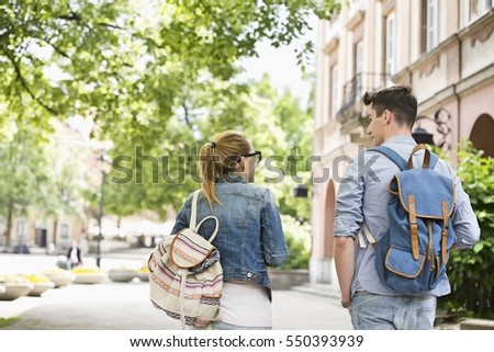 Rear view of young college friends talking while walking in campus