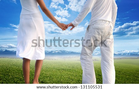 Rear view of young couple holding hands against landscape