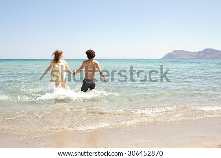 Rear view of young couple holding hands running into a clear sea on holiday, on the shore of a white sand beach with blue sky, outdoors. Travel and tourism lifestyle, honeymoon coastal destination.
