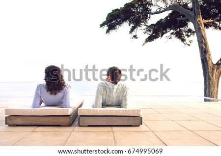Rear view of young couple relaxing on sunbeds by infinity pool