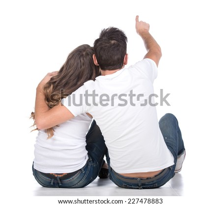 Rear view of young couple sit on ground back and point somewhere full length portrait isolated on studio white background
