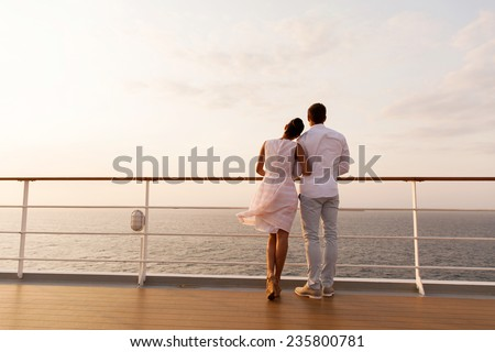 rear view of young couple standing on ship deck during sunset