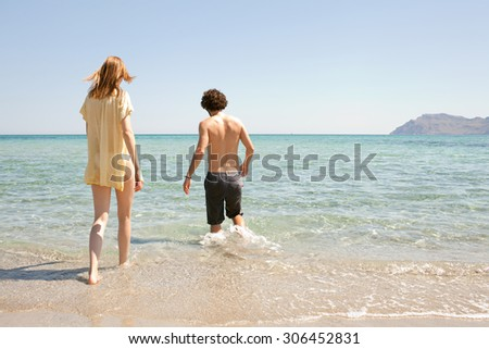 Rear view of young couple walking into the sea on holiday, on the shore of a white sand beach with blue sea water and sky, outdoors. Travel and tourism lifestyle, honeymoon coastal destination.