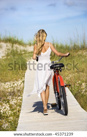 Rear view of young female as she walks her bike down a boardwalk. Vertical shot.