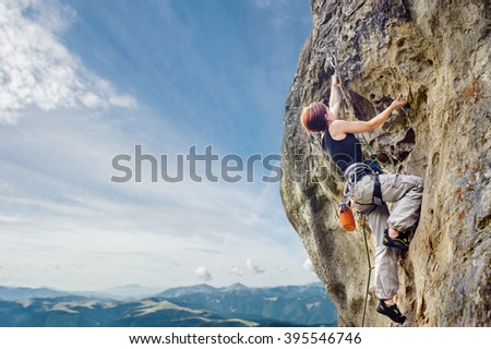 Rear view of young female climber climbing with rope and carbines, looking for next grip on a big rocky wall against blue sky and mountains. Summer time. Climbing equipment #395546746
