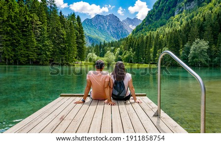 Rear view of young female sitting on wooden deck by beautiful lake in mountains  Green, spring, flower crown, outdoors  Zgornje Jezersko, Slovenia Stock photo ©