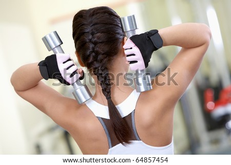 Rear view of young female with dumbbells doing exercises in gym