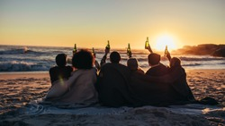 Rear view of young friends sitting at the beach with blanket raising beer bottle at the sunset. Group of friends having party celebrating and drinking at the beach in twilight sunset.