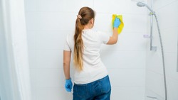 Rear view of young funny woman dancing while washing walls in bathroom and doing housework or home cleanup.