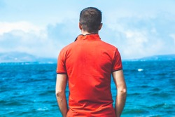 Rear view of young male traveler in shirt and shorts standing by the sea and enjoying nature and seclusion on a summer day