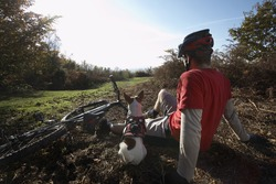 Rear view of young man and dog relaxing beside mountain bike in countryside