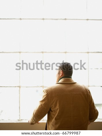 Rear view of young man looking out window