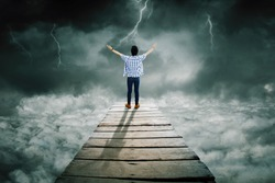 Rear view of young man looks bravery while standing on the wooden bridge and looking at lightning at cloudy sky