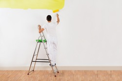 Rear view of young man painting wall with yellow paint roller at home