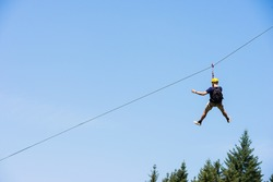 Rear view of young man riding on zip line against blue sky