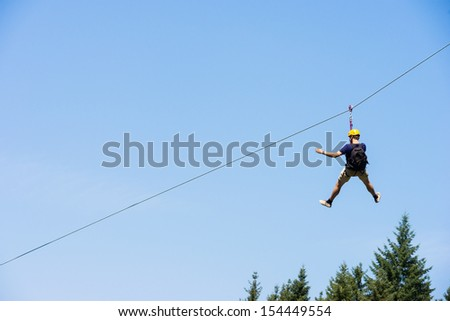 Photo of  Rear view of young man riding on zip line against blue sky