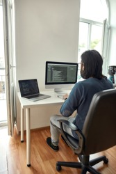 Rear view of young man, software developer writing code on desktop computer while sitting at his workplace and working from home. Freelance, stay home, self isolation. Web development