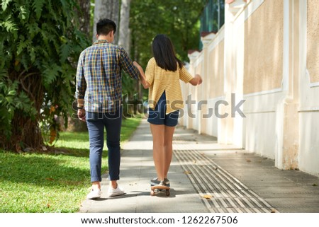 Rear view of young man teaching his girlfriend how to ride on skateboard #1262267506