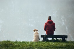 Rear view of young man with dog on lake lakeshore. Pet owner with his labrador retriever looking at lake during foggy weather.