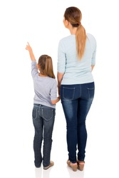 rear view of young mother and daughter pointing at empty space