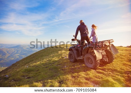Rear view of young pair near atv. Man is showing something in distance to her girlfriend. Stock photo ©