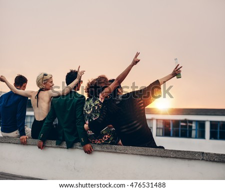 Rear view of young people partying on terrace with drinks at sunset. Young men and women enjoying drinks on rooftop in evening.
