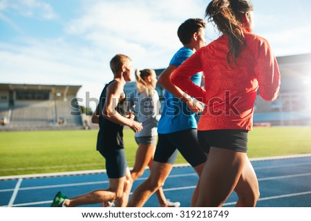 Rear view of young people running together on race track. Young athletes practicing a run on athletics stadium track.