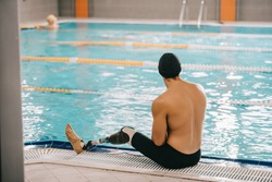 rear view of young swimmer with artificial leg sitting on poolside of indoor swimming pool