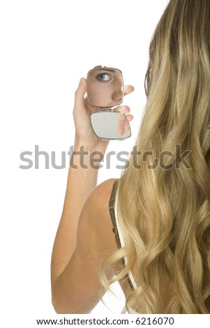 rear view of young woman holding up makeup compact. reflection of her eye visible in mirror. - stock photo
