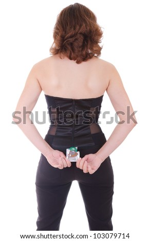 rear view of young woman in black holding a green condom, isolated on white background