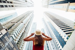 Rear view of young woman in red dress holding with both hands straw hat amazed looking up on skycrapers at downtown in modern city.