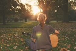 Rear view of young woman sitting on the grass and playing guitar in the park at sunset