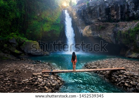 Rear view of young woman standing in front of waterfall with her hands raised. Female tourist with her arms outstretched looking at waterfall. #1452539345