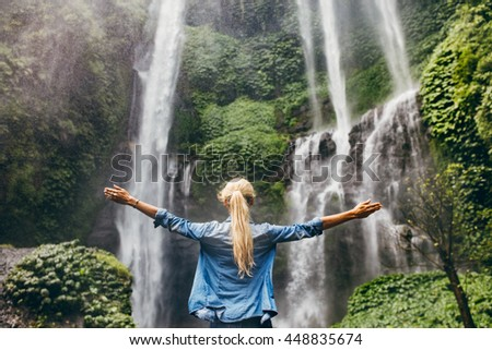 Rear view of young woman standing in front of waterfall with her hands raised. Female tourist with her arms outstretched looking at waterfall. stock photo