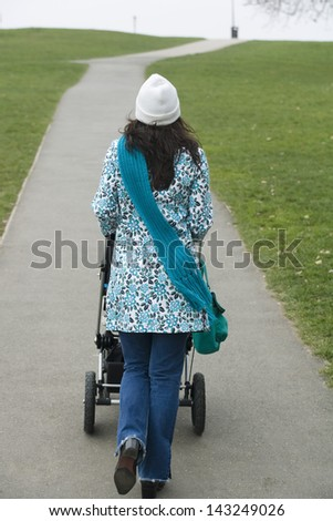 Rear view of young woman walking with baby carriage in park