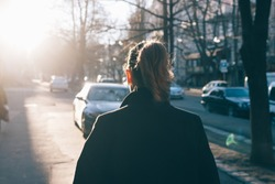 Rear view of young woman wearing black coat walking down the street, sun shine against her. A girl with a ponytail hairstyle goes along the autumn city.