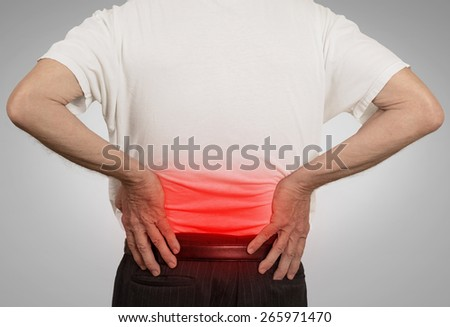 rear view old man grandpa holding his painful lower back colored in red with hands isolated on gray background. Human health problems