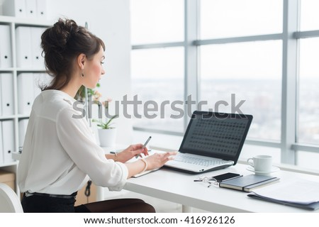 Rear view portrait of a businesswoman sitting on her workplace in the office, typing, looking at pc screen.