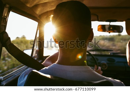 Rear view portrait of man travels drive in a car for adventures. Unrecognizable back view. Sunset flares coming from windscreen. Lifestyle and travel concept.