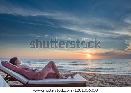Rear view portrait of relaxed woman watching photos on her mobile phone while relaxing on sunbed on the beach.  #1281056050