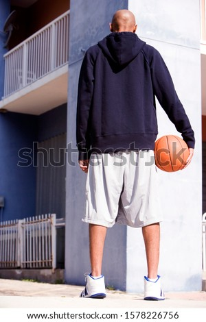 Rear view portrait of young African American man holding a basketball