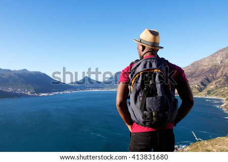 Rear view portrait of young african man on holiday with hat and backpack looking at the sea