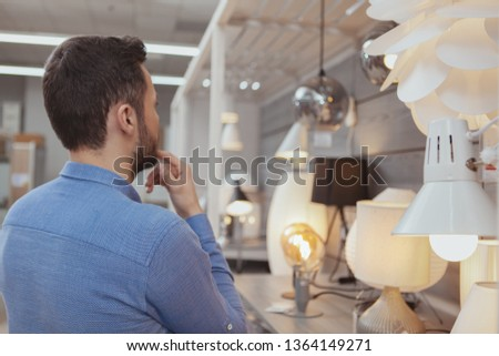 Rear view shot of a male customer choosing lighting for his apartment at department store, copy space. Man buying environmentally friendly efficient lamps. Retail, consumerism, home concept