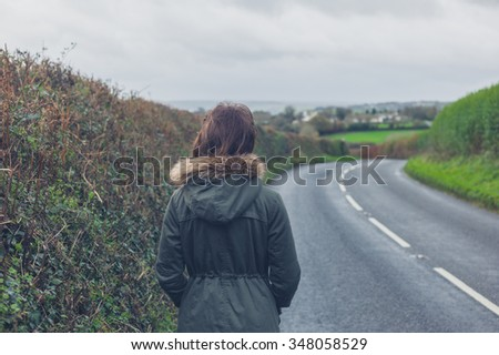 Rear view shot of a young woman walking on a country road by herself in the autumn or winter