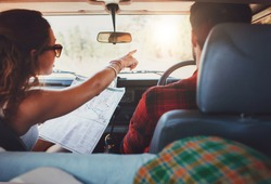 Rear view shot of couple driving on country road. Woman holding map and showing the route map to her boyfriend driving the car. Couple on a road trip.