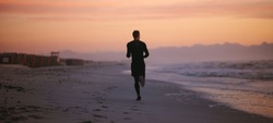 Rear view shot of fit man running on the sea shore in morning. Healthy male athlete running along the beach.